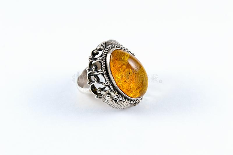 Silver Amber Ring. Original silver ring with yellow amber stone on top. Crafted by skilful jeweller and a mighty goldsmith. Grey, shiny silver with deep yellow royalty free stock photo