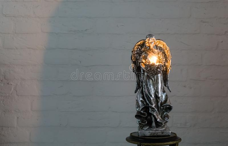 A silver angel sculpture holding a lighted tea light candle, a christmas and spiritual tradition. Silver angel sculpture holding a lighted tea light candle, a stock photos
