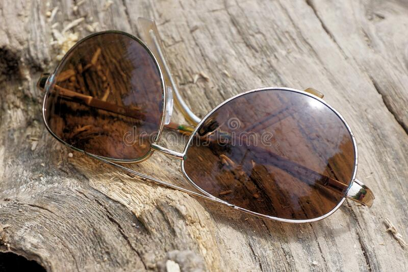 Silver Aviator Sunglasses on Top of Wooden Surface stock image