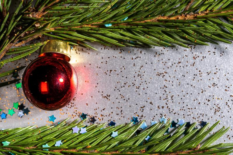 a silver background sprinkled with bright stars and glitter and on which spruce twigs and a Christmas red royalty free stock photos