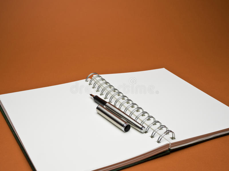 Silver ball point pen on white sketchbook with red background. White sketchbook with silver metallic ball point pen on red background stock photography