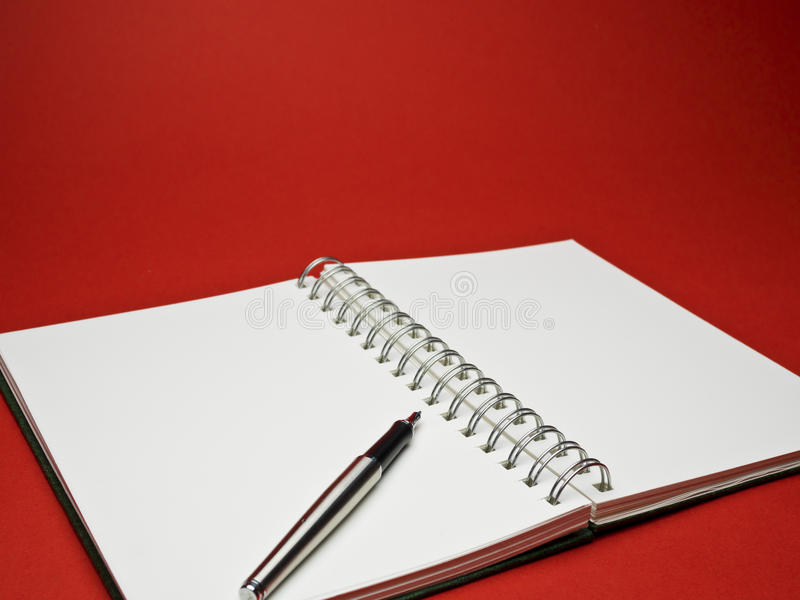 Silver ball point pen on white sketchbook with red background. White sketchbook with silver metallic ball point pen on red background royalty free stock photos