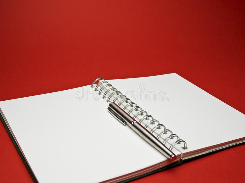Silver ball point pen on white sketchbook with red background. White sketchbook with silver metallic ball point pen on red background stock photo