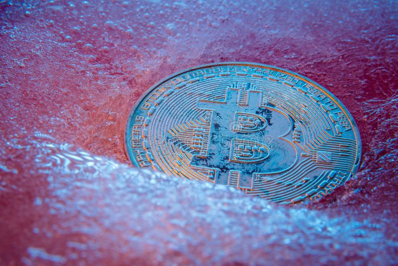 Silver Bitcoin, bit coin online digital currency frozen in the blue ice. Concept of block chain, crypto market crash. Frozen stock photography