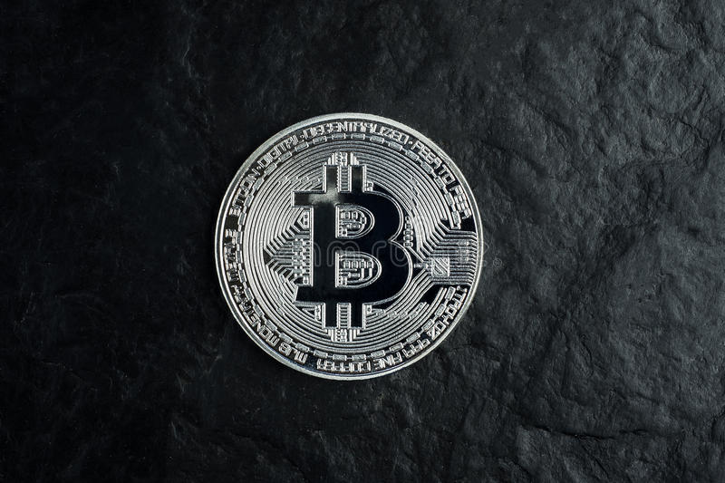 Silver bitcoin on black stone table background with texture, hard and solid, dark, isolated royalty free stock photo