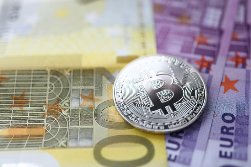 Silver bitcoin with euro cash lie on the table stock photography