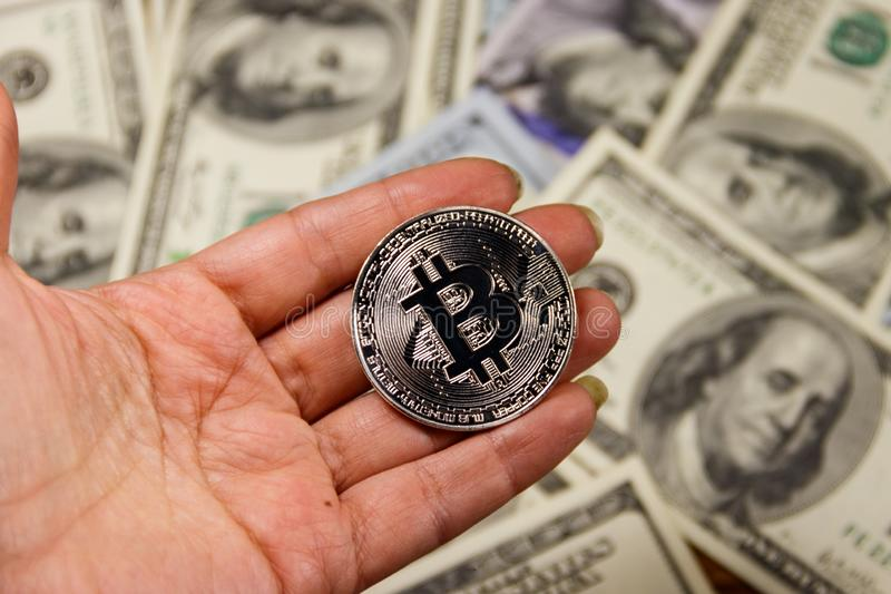 Silver bitcoin in hand against one hundred dollar bills royalty free stock photo