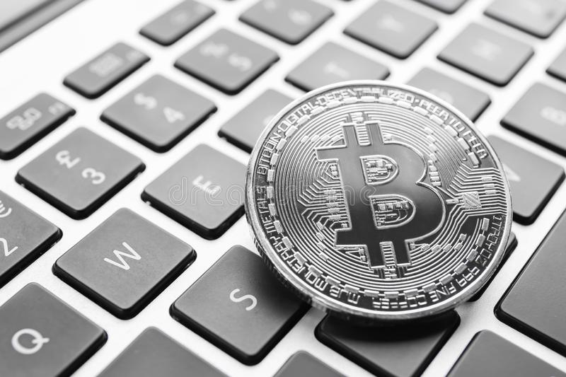 Silver bitcoin on PC keyboard royalty free stock images