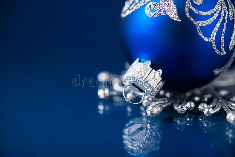 Silver and blue christmas ornaments on dark blue background with space for text. Merry christmas card. royalty free stock images