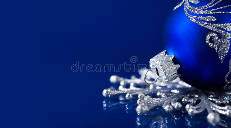 Silver and blue christmas ornaments on dark blue background royalty free stock photography