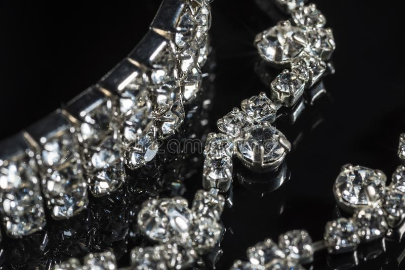 Silver bracelet and necklace with diamonds on black background close-up stock photos