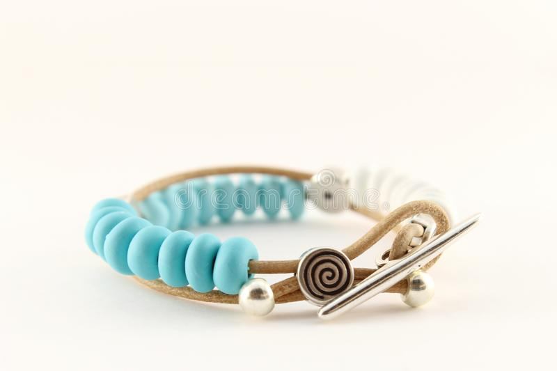 Silver bracelet, with turquoise polymeric clay, and leather cord stock image