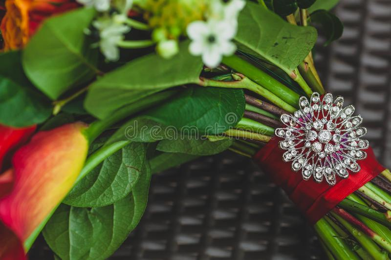 A silver brooch with rhinestones on the stalk of the wedding bouquet with red ribbons. Close-up. Artwork royalty free stock photo