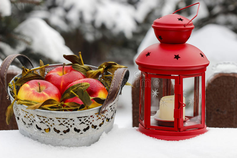 Silver bucket of apples and red lantern on snow