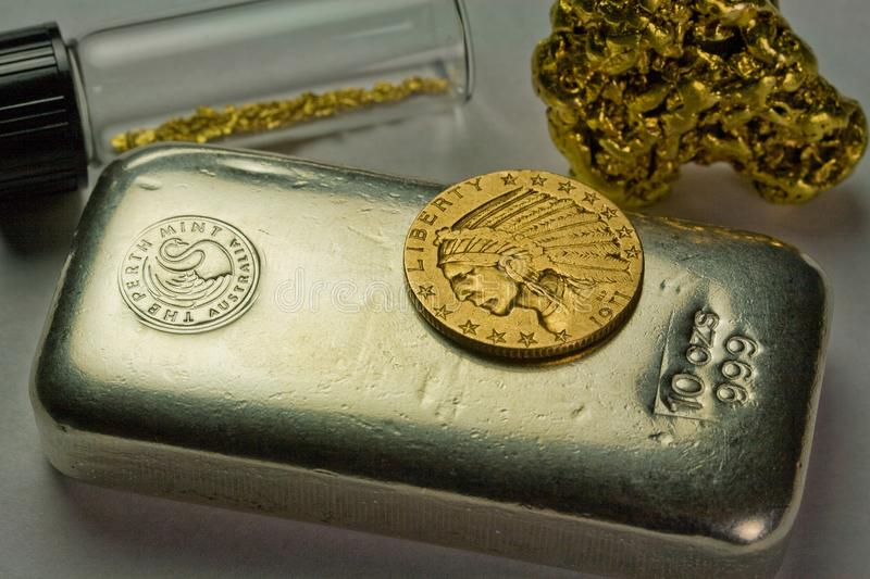 Silver Bullion Bar, Gold Coin and Gold Nuggets. 10 ounce silver bullion bar, $5 Indian Gold Coin and natural gold nuggets - Precious metals stock images
