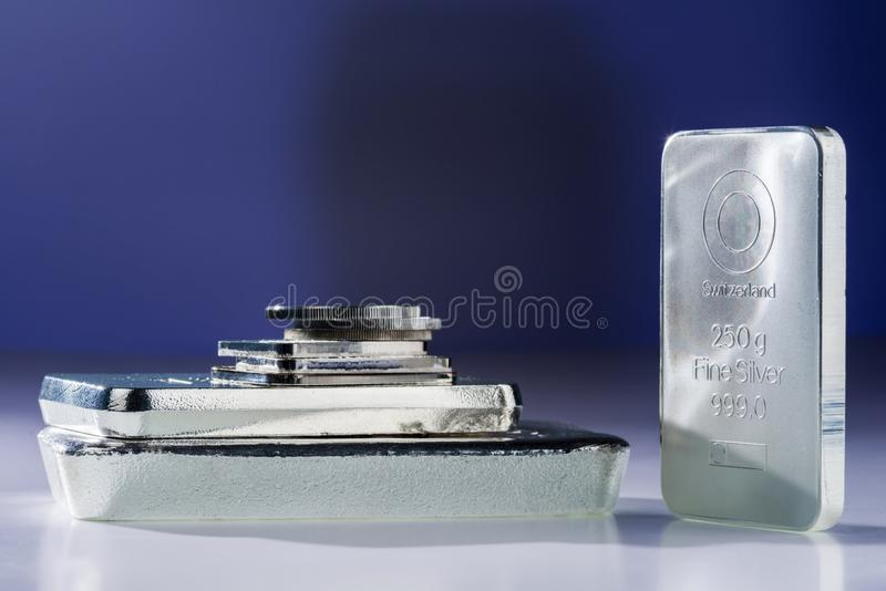 Silver bullion. Cast and minted bars and coins on a gray-purple background royalty free stock photo