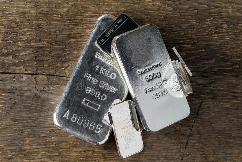 Silver bullion on wooden texture background. Silver bullion on wood texture background. Different coins and bars stock photography