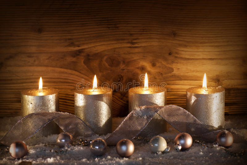Silver candles for the 4. Advent. Still life with silver candles for the 4. advent in front of a wooden wall stock photo
