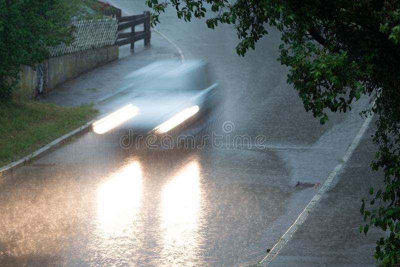 Silver Car driving the street down in the rain stock image