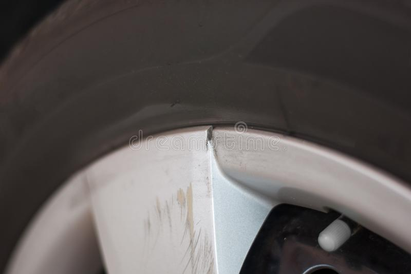 Silver car tire rim is broken and scratched because of hitting s stock image