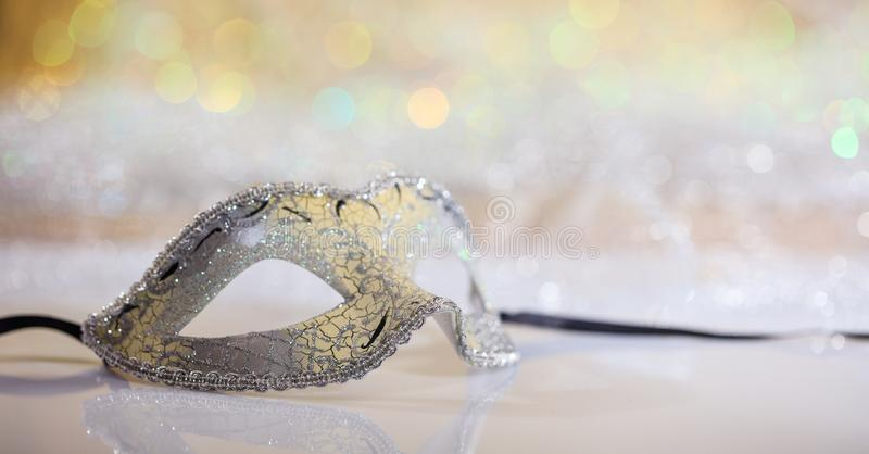 Silver carnival mask on bokeh background. Silver carnival mask on white surface, abstract bokeh background royalty free stock photography