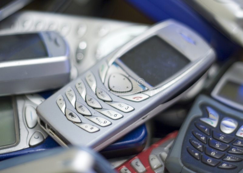 Silver cell phone in pile of others. royalty free stock images