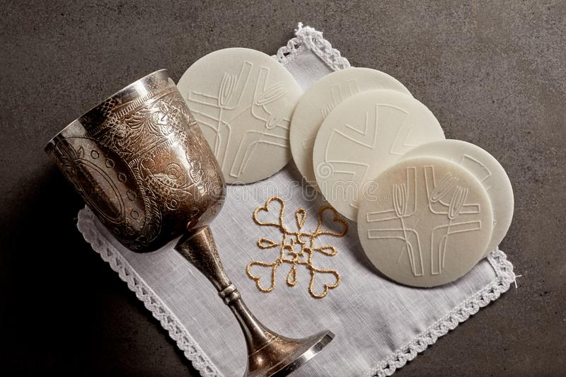 Silver chalice cup and Sacramental bread. Or Hosties, symbolising the blood and body of the resurrected Christ for the Communion Service stock photography