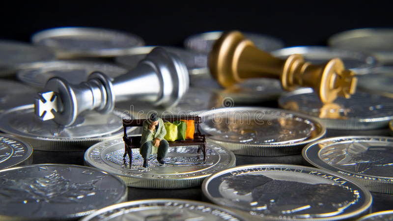 Silver chess with homeless man, detail. Silver chessboard, silver and gold chess, silver coins with black background, homeless sitting on the bank stock photo