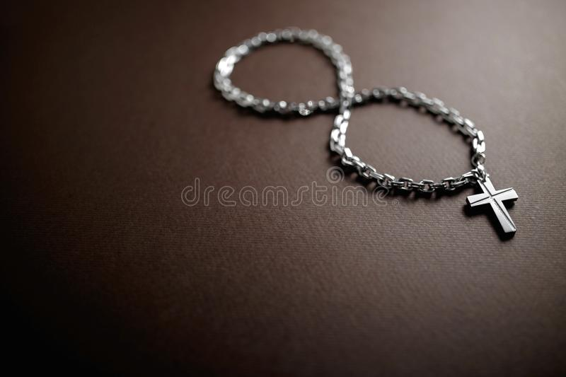 Silver christian cross and chain on brown background with infinite symbol. royalty free stock images