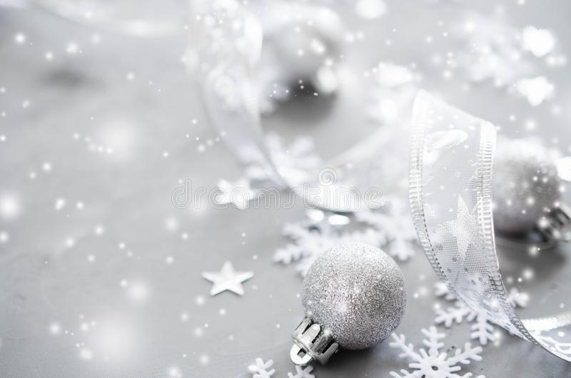 Silver Christmas background. Curly ribbon with decorative balls and snowflakes. royalty free stock photos