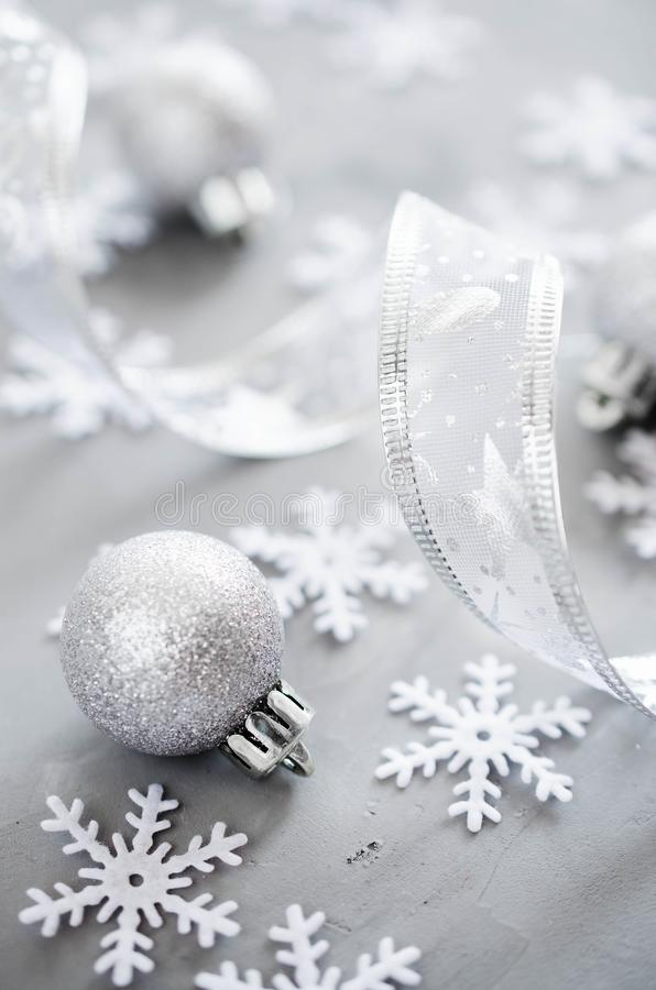 Silver Christmas background. Curly ribbon with decorative balls and snowflakes. stock photos