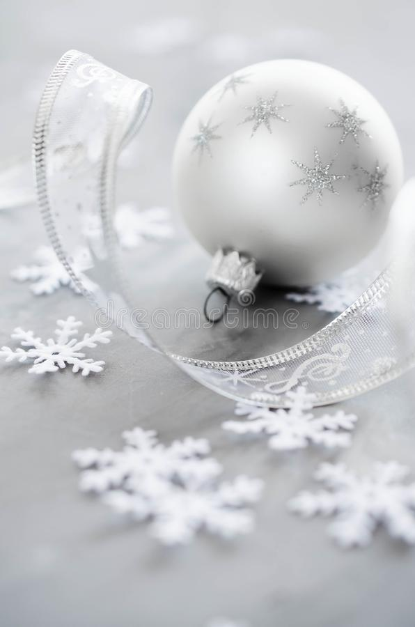 Silver Christmas background. Curly ribbon with decorative balls and snowflakes. stock images