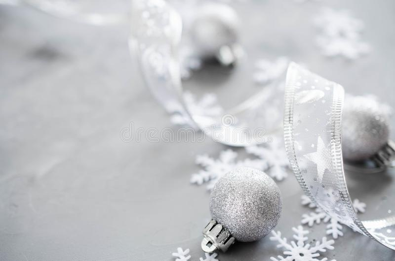 Silver Christmas background. Curly ribbon with decorative balls and snowflakes. stock photography