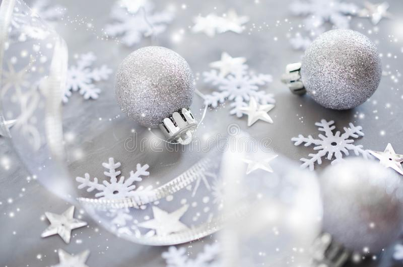 Silver Christmas background. Curly ribbon with decorative balls and snowflakes. royalty free stock image