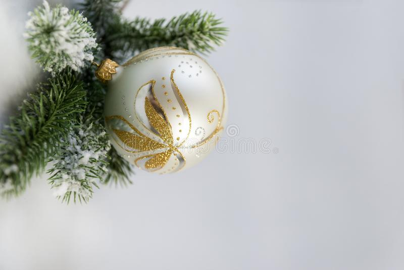 Silver Christmas ball with a Golden pattern with a green spruce. 1 silver Christmas ball with a Golden pattern with a green spruce branch on a gray blue royalty free stock photo