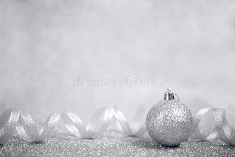 Silver christmas ball. And ribbon on shiny glitter background close-up stock images