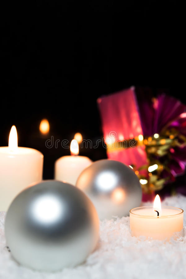 Silver christmas balls, candles and a red gift in the snow royalty free stock photography