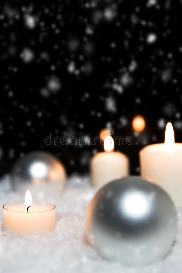 Silver christmas balls and candles in the snow, snowing background royalty free stock image