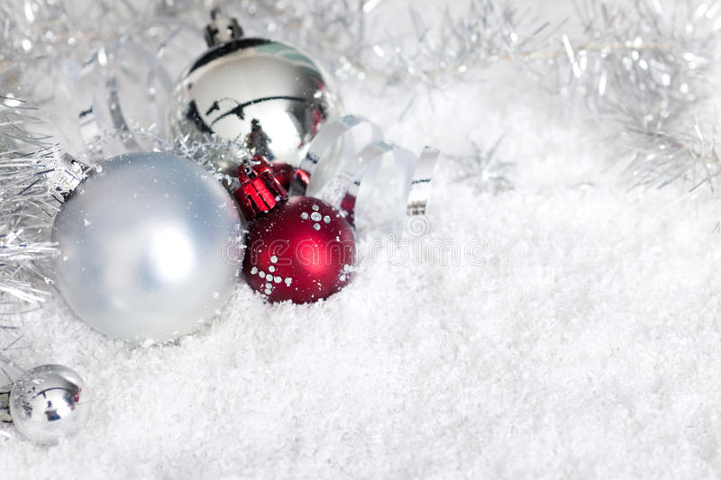 Silver christmas balls in snow stock image
