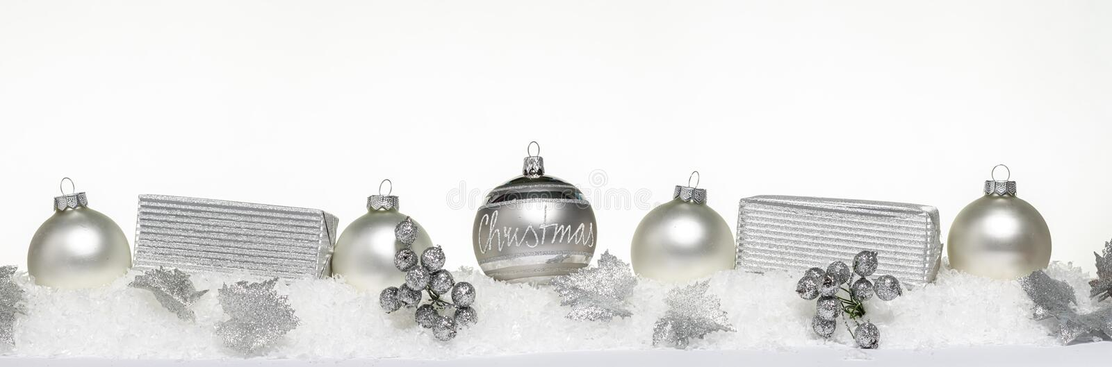 Silver christmas balls with xmas present gift boxes in a row isolated on snow. 2 royalty free stock photos