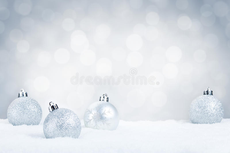 Silver Christmas baubles on snow with. Defocused silver and white lights in the background. Shallow depth of field stock image