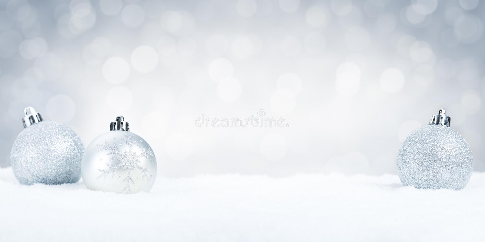 Silver Christmas baubles on snow with a silver background. Silver Christmas baubles on snow with defocused silver and white lights in the background. Shallow stock photography