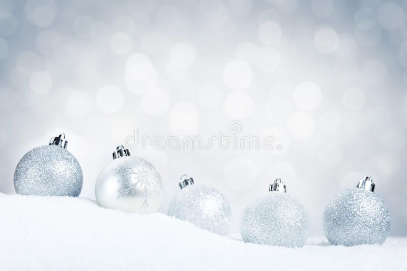 Silver Christmas baubles on snow with a silver background. A row of silver Christmas baubles on snow with defocused silver and white lights in the background royalty free stock photography