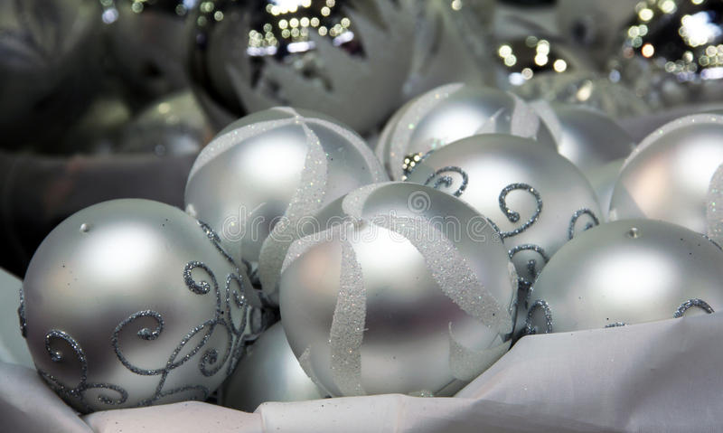 Silver Christmas bumps. Christmas silver bumps for a Christmas tree with handmade Trilogy on a gray reflective surface royalty free stock photo