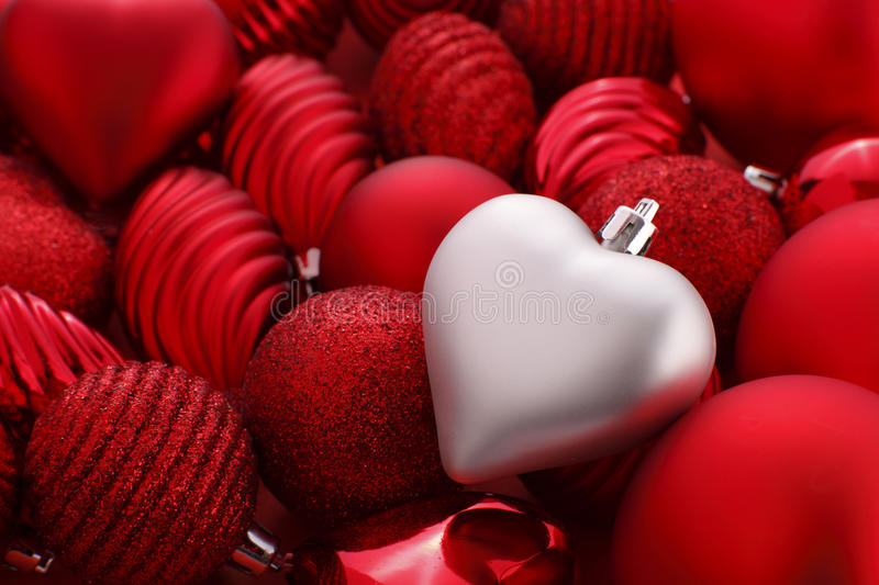 Silver christmas heart. On red baubles stock image