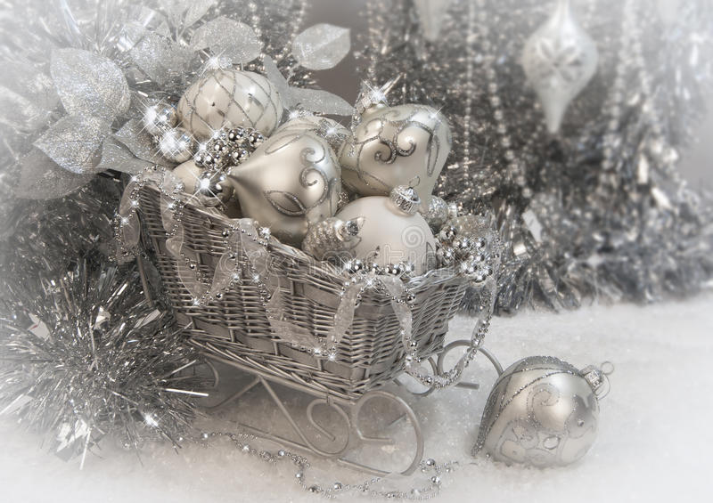 Silver Christmas Sleigh. A silver Christmas sleigh filled with various silver ornaments, silver foliage and surrounded with silver tinsel royalty free stock image