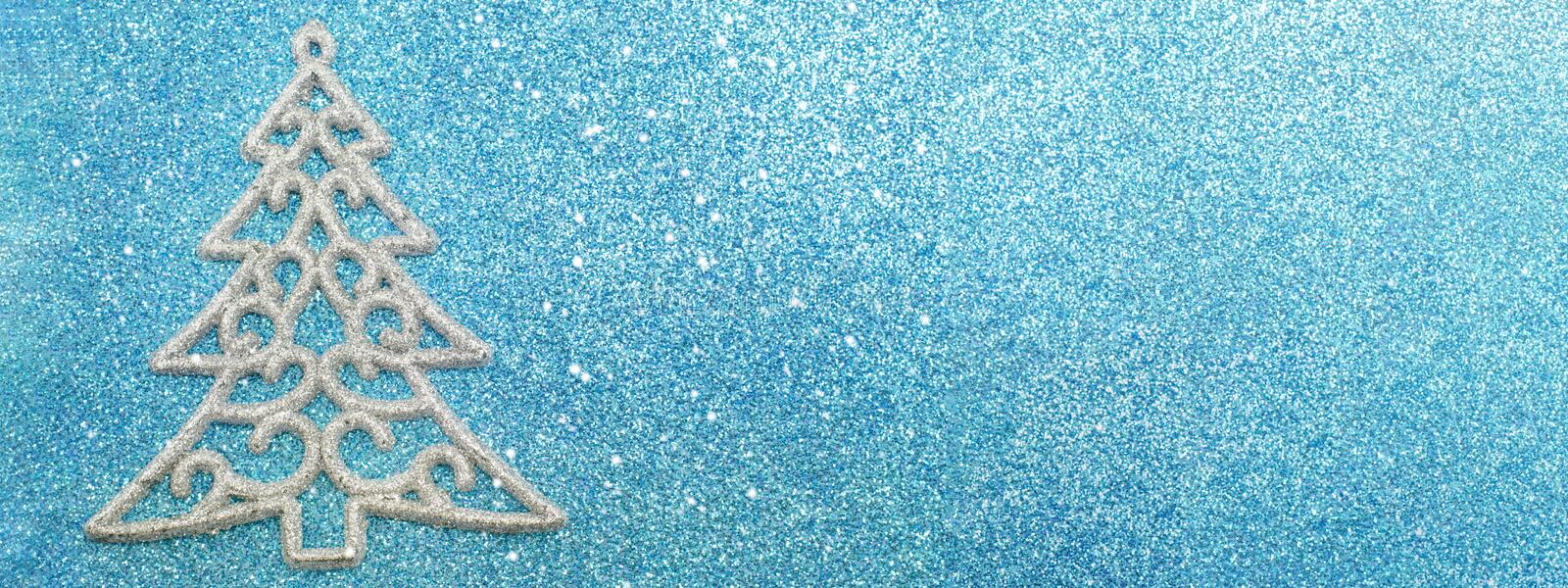 Silver Christmas tree decoration on blue background stock photography