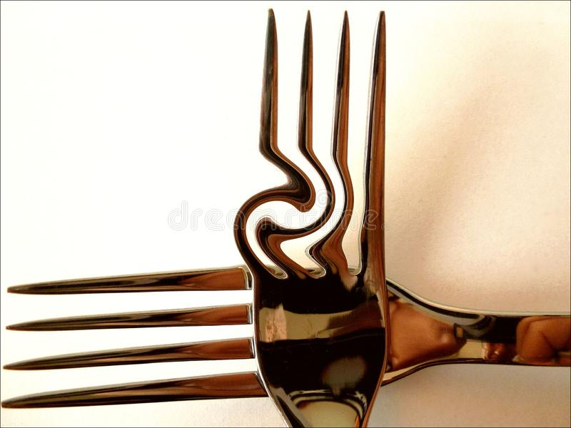 Shiny chrome finished abstract forks in a cross shape royalty free stock image