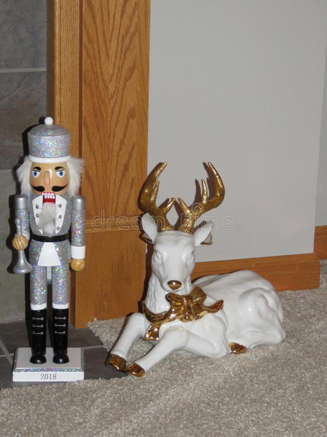 Silver clad nutcracker and gold trimmed white porcelain deer stock photo