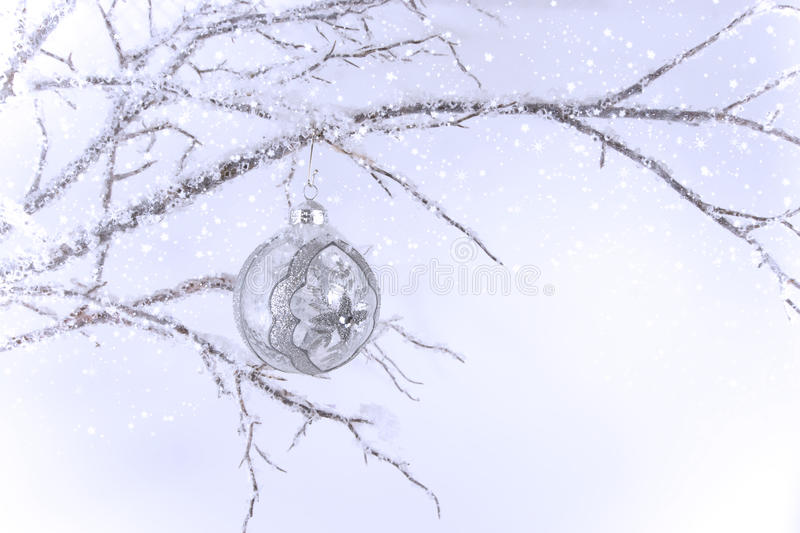 Silver & Clear Christmas Ornament on Branch. A silver and clear glass Christmas ornament hanging from crystal covered branch. Background light blue with falling stock image